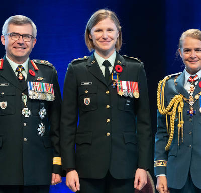 Recipient Lieutenant-Colonel Claire Katherine Bramma stands between the Vice Chief of the Defence Staff,   Lieutenant-General Paul Wynnyk (on the left) and Her Excellency the Right Honourable Julie Payette (on the right).