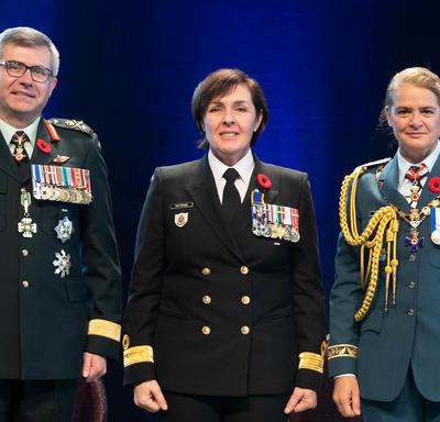 Le capitaine de vaisseau Rebecca Louise Patterson se tient entre le Vice-chef d'état-major de la Défense, le   Lieutenant-général Paul Wynnyk (à gauche) et Son Excellence la très honorable Julie Payette (à droite).