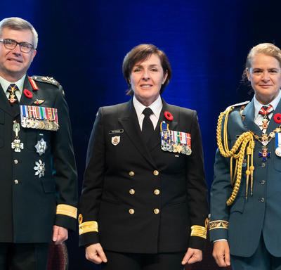 Recipient Captain(N) Rebecca Louise Patterson stands between the Vice Chief of the Defence Staff, Lieutenant-  General Paul Wynnyk (on the left) and Her Excellency the Right Honourable Julie Payette (on the right).