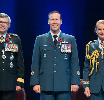 Recipient Warrant Officer Aaron David Bygrove stands between the Vice Chief of the Defence Staff, Lieutenant-  General Paul Wynnyk (on the left) and Her Excellency the Right Honourable Julie Payette (on the right).