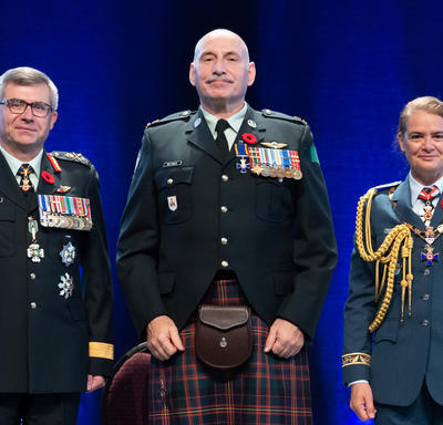 Recipient Major James Edward Rene MacInnis stands between the Vice Chief of the Defence Staff, Lieutenant-General   Paul Wynnyk (on the left) and Her Excellency the Right Honourable Julie Payette (on the right).