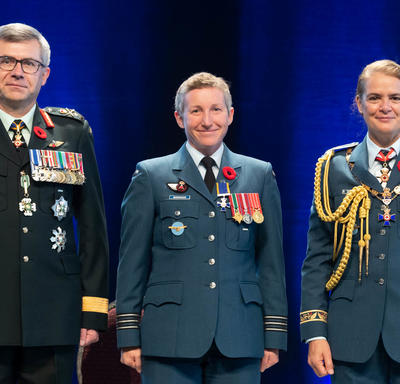 Recipient Major Jennifer Lynn Morrison stands between the Vice Chief of the Defence Staff, Lieutenant-General Paul   Wynnyk (on the left) and Her Excellency the Right Honourable Julie Payette (on the right).