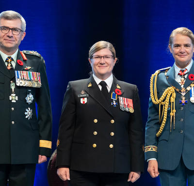 Recipient Chief Petty Officer 2nd Class Marie Nathalie Isabelle Scalabrini stands between the Vice Chief of the   Defence Staff, Lieutenant-General Paul Wynnyk (on the left) and Her Excellency the Right Honourable Julie Payette   (on the right).