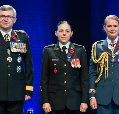 Recipient Sergeant Roxane St. Michael stands between the Vice Chief of the Defence Staff, Lieutenant-General Paul   Wynnyk (on the left) and Her Excellency the Right Honourable Julie Payette (on the right).