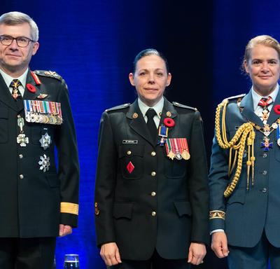 Le sergent Roxane St. Michael se tient entre le Vice-chef d'état-major de la Défense, le Lieutenant-général Paul   Wynnyk (à gauche) et Son Excellence la très honorable Julie Payette (à droite).