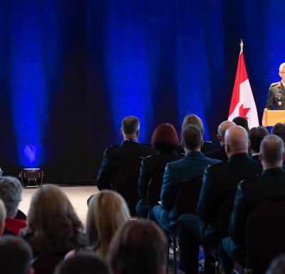 The Vice Chief of the Defence Staff, Lieutenant-General Paul Wynnyk stands in front of a podium and addresses the   crowd, largely in military uniform.  Her Excellency the Right Honourable Julie Payette is seated and is listening   to the speech.
