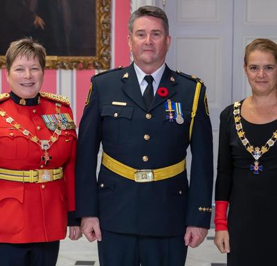 The Governor General and the Commissioner of the RCMP take a photo with a recipient of the Order of Merit of the Police Forces.