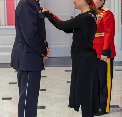 The Governor General pins a medal on the chest of a recipient of the Order of Merit of the Police Forces.