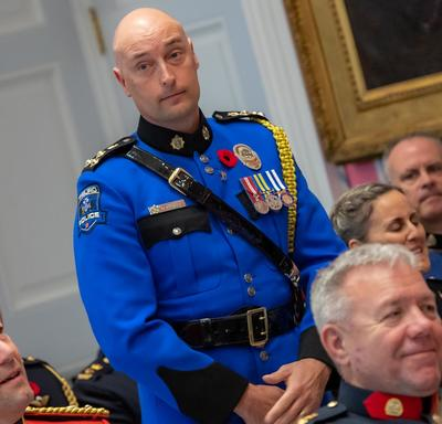 A recipient of the Order of Merit of the Police Forces stands before approaching the front of the room to accept his medal.