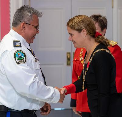 The Governor General shakes hands with a recipient of the Order of Merit of the Police Forces.