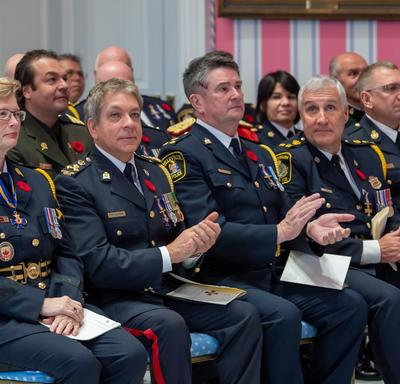 Recipients of the Order of Merit of the Police Forces sit together during an investiture ceremony.