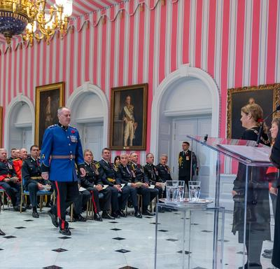 A recipient of the Order of Merit of the Police Forces walks to the front of the tent room to accept his medal.