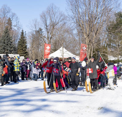 There is a large crowd standing outdoors in winter.  In the center of the photo are two rows of people strapped to large multi-persons cross-country skis.  They are at a start line getting ready to being a friendly race.