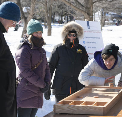 A young man wearing a tuque and a winter coat plays a game with wooden pieces.  Her Excellency stands behind him, smiling, in her winter coat.