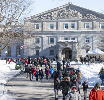 The front façade of Rideau Hall. In front of the residence is a large group of people all dressed in winter gear, walking along the main path.