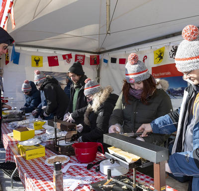 Half a dozen volunteers in winter gear serve raclette to visitors.