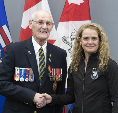 Her Excellency is shaking hands with Edward MacPherson.