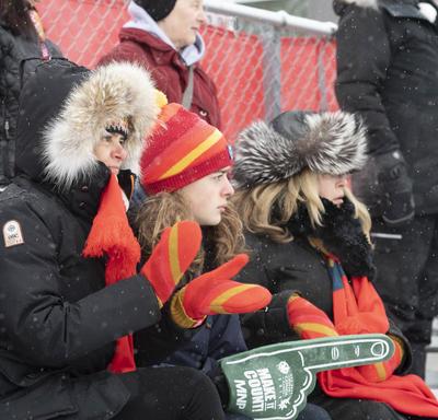 La gouverneure générale est assise dans les gradins pour encourager les patineurs de vitesse.
