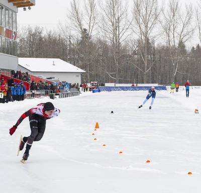 Les patineurs de vitesse masculins compétitionnent.