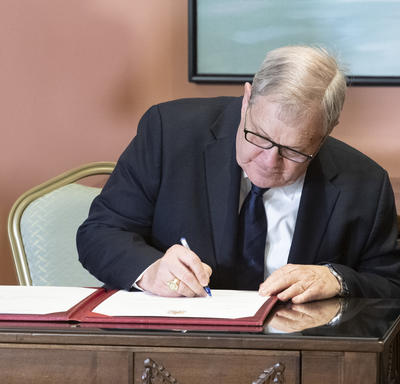 Lawrence MacAulay is sitting at a desks and signing a register.