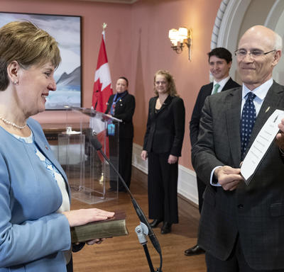 Marie-Claude Bibeau stands in front of the Michael Wernick, clerk of the Privy Council, who holds up the Oath of Office. Her right hand is placed on a Bible.  Behind them stand Prime Minister Justin Trudeau, Governor General Julie Payette and the MC.