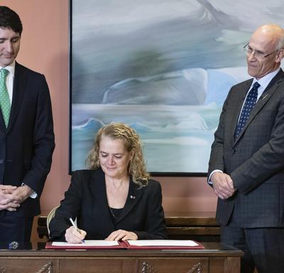 La gouverneure générale Julie Payette s'assoit à un bureau et signe un registre.  Derrière elle, le premier ministre Justin Trudeau, à sa droite, et Michael Wernick, greffier du Conseil privé, à sa gauche.