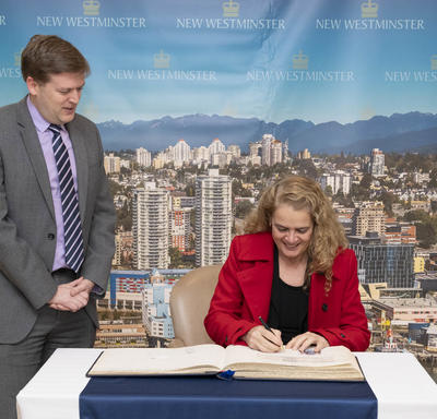 The Governor General signs the city`s guest book while the mayor stands beside her.