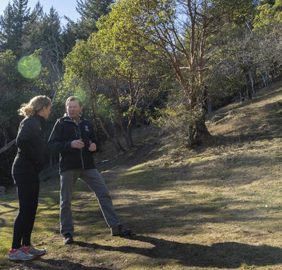 The Governor General and Jamie Cassels, President of the University of Victoria, are talking to each other during a hike.