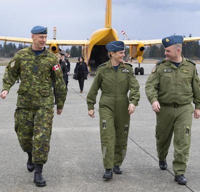 La gouverneure générale marche côte à côte avec les membres de la FCA qui descendent de l'avion.