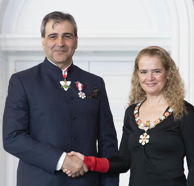 Mohit Bhandari, shakes the Governor General's hand.  They smile at the camera and are both wearing their Order of Canada insignia