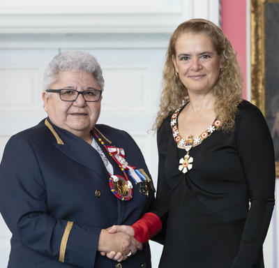 Marie-Anne Day Walker-Pelletier shakes the Governor General's hand.  They smile at the camera and are both wearing their Order of Canada insignia.