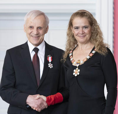 Raymond L. Desjardins shakes the Governor General's hand.  They smile at the camera and are both wearing their Order of Canada insignia