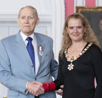 David Fox shakes the Governor General's hand.  They smile at the camera and are both wearing their Order of Canada insignia.