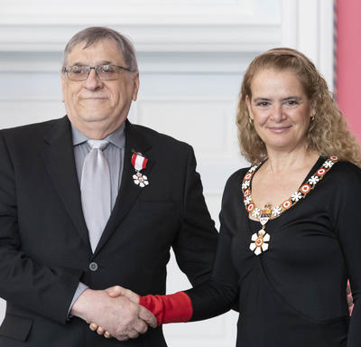 Laurier Gareau shakes the Governor General's hand.  They smile at the camera and are both wearing their Order of Canada insignia.