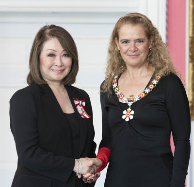 Mutsumi Takahashi shakes the Governor General's hand.  They smile at the camera and are both wearing their Order of Canada insignia