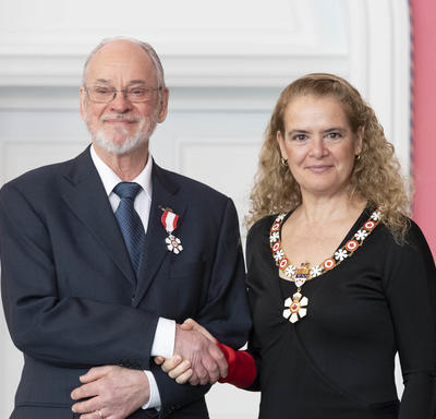 Barry Wellar shakes the Governor General's hand.  They smile at the camera and are both wearing their Order of Canada insignia