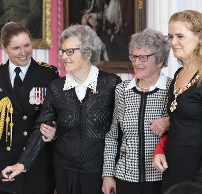 Isabella Rhoda Wurtele Eaves stands center right and her twin sister, Grace Rhona Wurtele Gillis, center left.  They are flanked by the Governor General on the right and a young military officer to the left.
