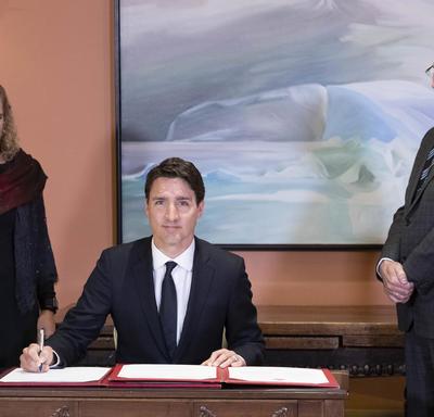 Le premier ministre signe le livre des serments. Le gouverneur général et le greffier du Conseil privé à ses côtés.