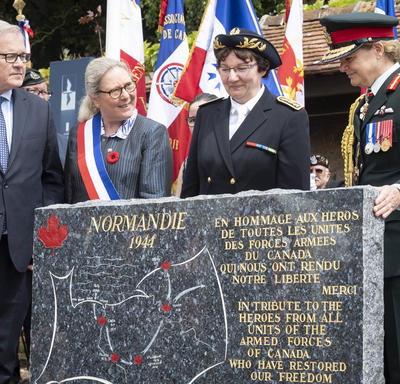 The Governor General and others stand around the monument.