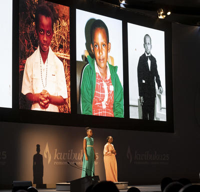 Pictures of children are displayed on a screen on the stage.