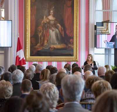A photo of the room with the Governor General standing at the front.