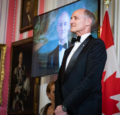 Colm Feore stands on stage to receive his award.