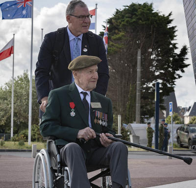 A war veteran in a wheelchair, wearing a beret and war medals, is pushed by a man. Several flags are in the background.