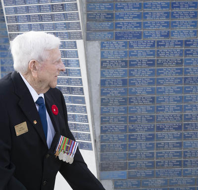 An elderly gentleman is walking on front of a monument.