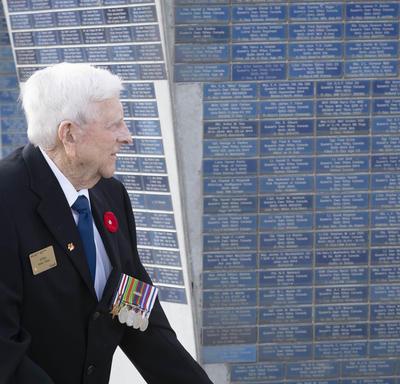 Un homme âgé marche devant un monument.