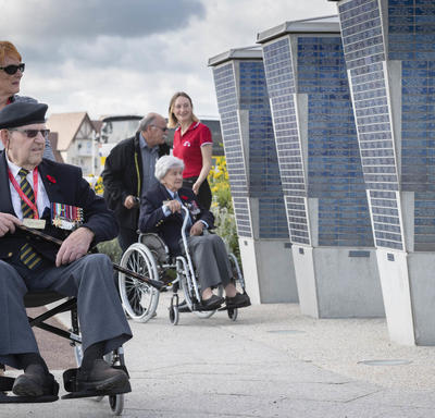 Two elderly people in wheelchairs, each pushed by a another person, pass in front of a monument.