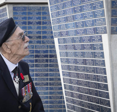 An elderly man lifts his head to look at a monument.