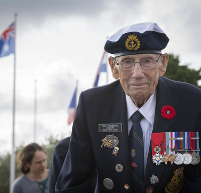 A veteran looks straight at the camera. The sky is gray behind him.