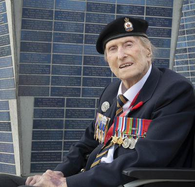 A veteran, wearing several medals is seated in a wheelchair, looking directly at the camera. a tall monument is behind him.