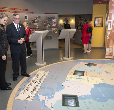 Governor General Julie Payette stands in a room while looking at a map on the floor in front of her. A man standing to her left is giving her explanations on what she is seeing.